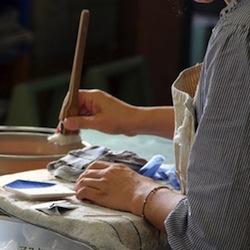 転写紙に印刷された柄をお皿に当てて、裏面を水に濡らした刷毛でこすります。紙を剥がすと、あらびっくり。乾いていた素焼きの皿の表面に吸い付く様に柄が移っています。
