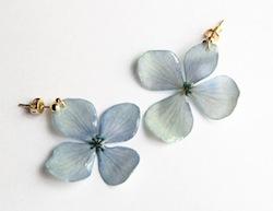 季節の生花を押し花にして、樹脂で固めて金具をつけていきます。